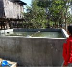 Mrs. Leakhana is filling the brick-made fish tank with water in Kamphun village, Stung  Treng