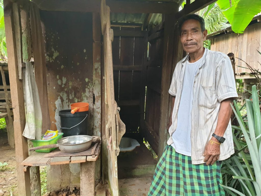 Khmer man standing in front of latrine ODF