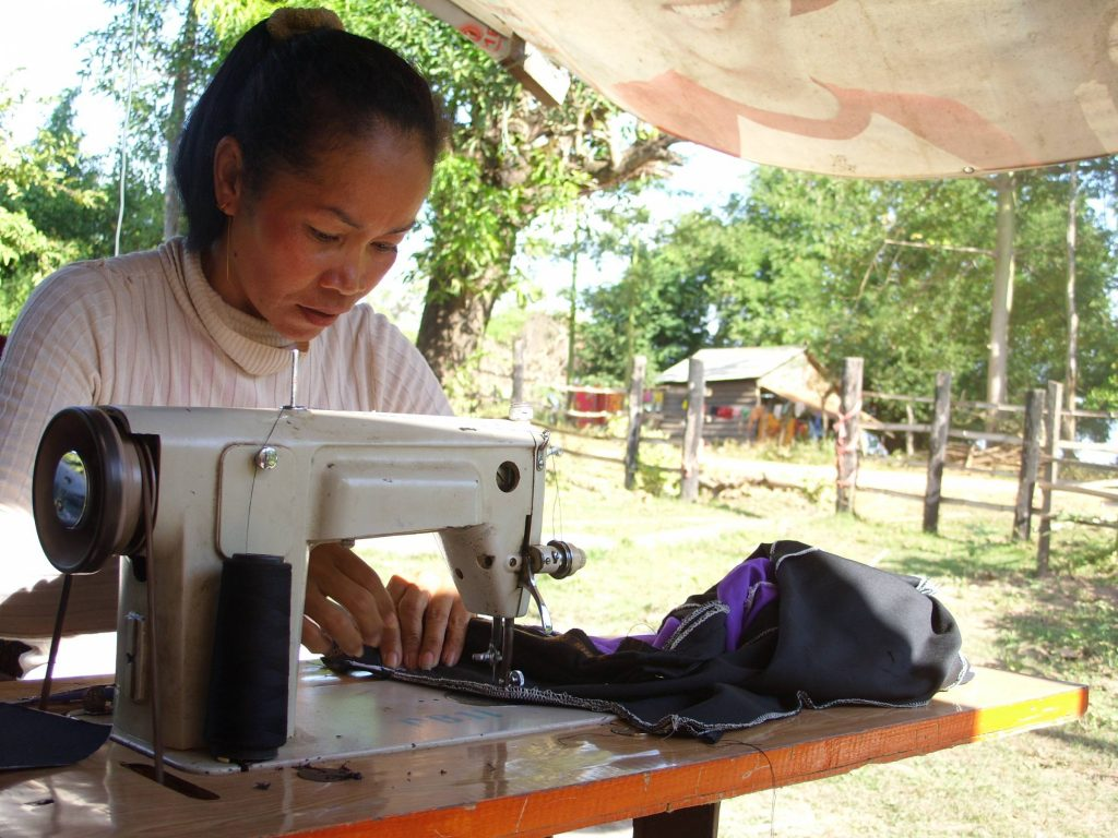 Cambodian woman sewing machine making clothes tailor business